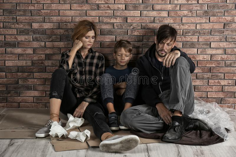 Poor homeless family sitting on floor stock photos