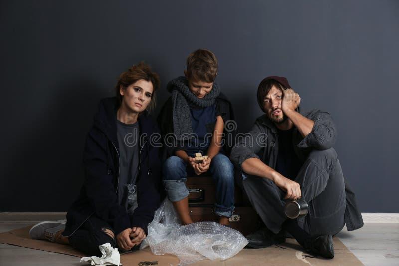 Poor homeless family sitting on floor. Near dark wall royalty free stock image
