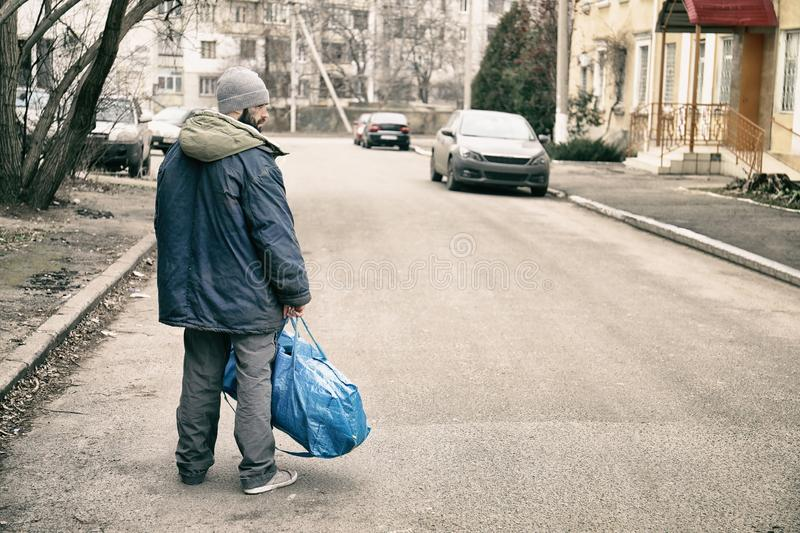 Poor homeless man with bag on street royalty free stock photography
