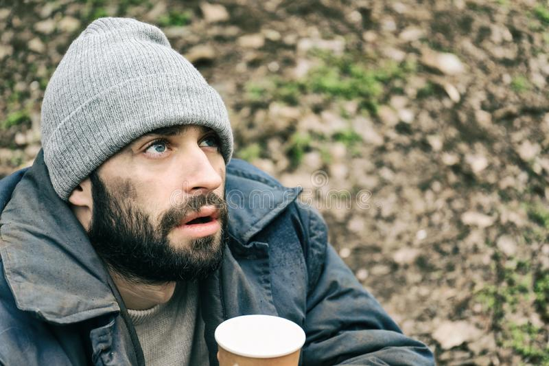 Poor homeless man with cup in  park royalty free stock image