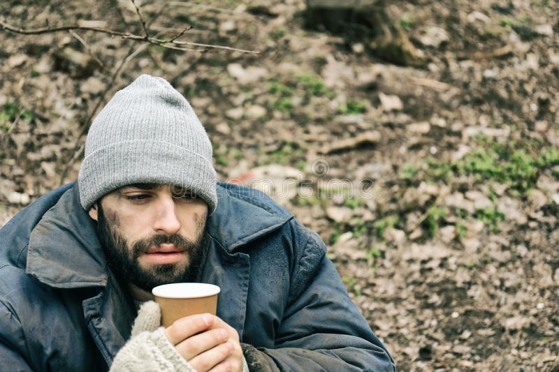 Poor homeless man with cup in park royalty free stock photos