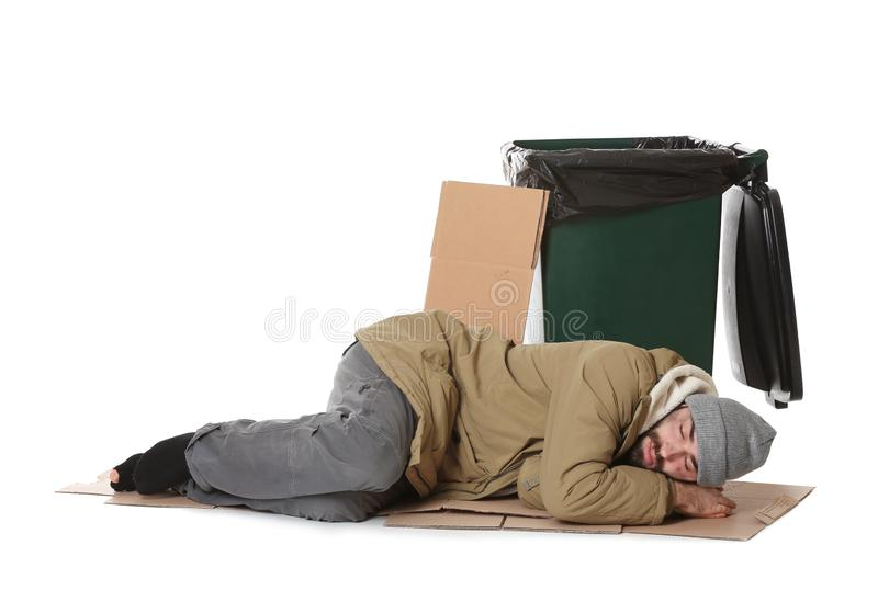 Poor homeless man lying near trash bin. Isolated on white royalty free stock photography