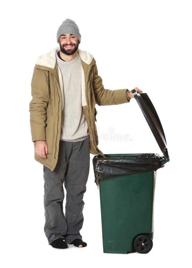 Poor homeless man near trash bin isolated on. White stock image