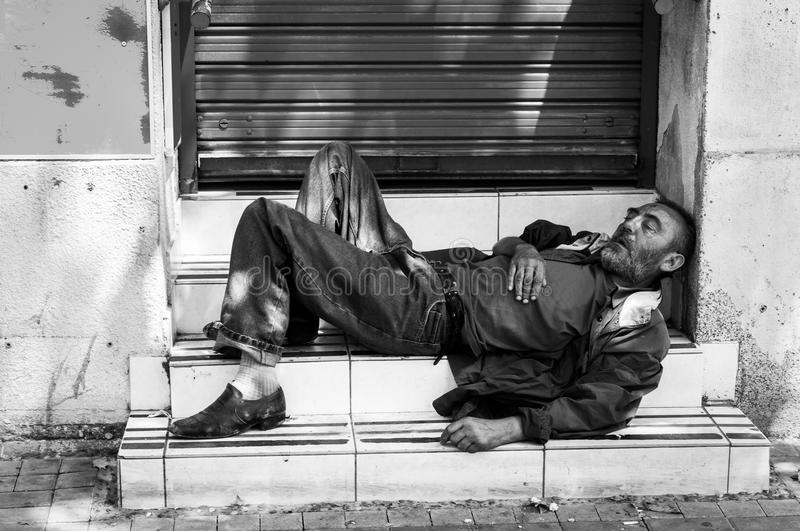 Poor homeless man or refugee sleeping on the stairs on the street, social documentary concept black and white royalty free stock photography