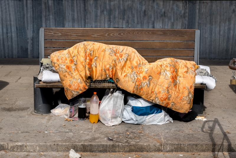 Poor homeless man or refugee sleeping on the wooden bench on the urban street in the city covered with a blanket with bags of clot royalty free stock image
