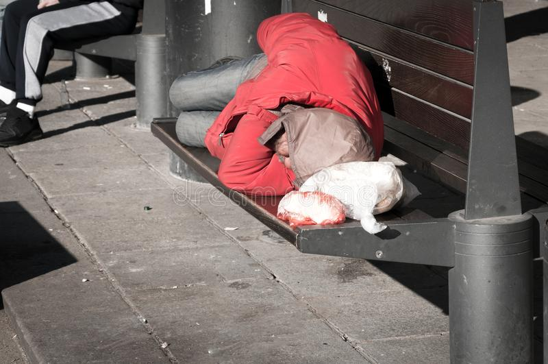 Poor homeless man or refugee sleeping on the wooden bench on the urban street in the city, social documentary concept stock photos