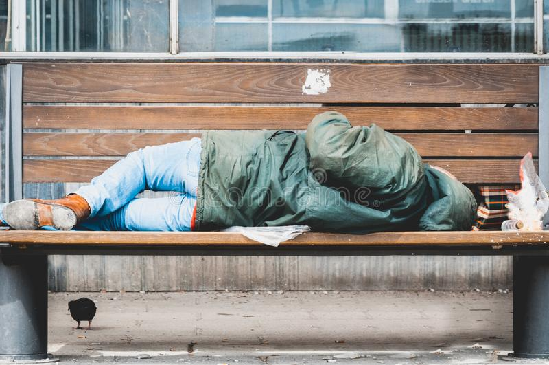 Poor homeless man or refugee sleeping on the wooden bench on the urban street in the city, social documentary concept stock photo