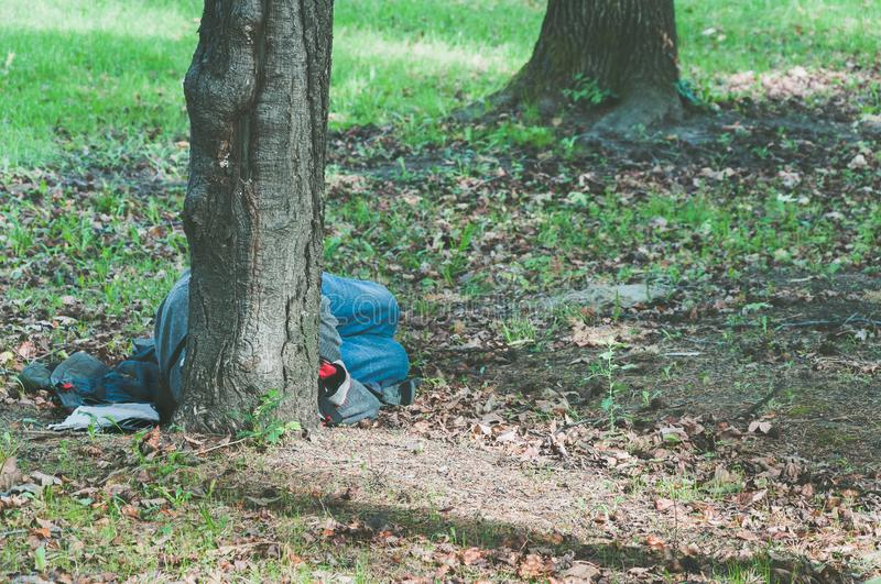 Poor homeless refugee man sleeps on the ground of the park in the city. royalty free stock photo