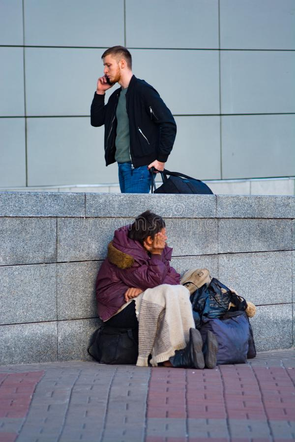 Poor homeless woman and succesful man near the train station. Central Train Station, 15.10.2018 Ukraine, Kiev royalty free stock images