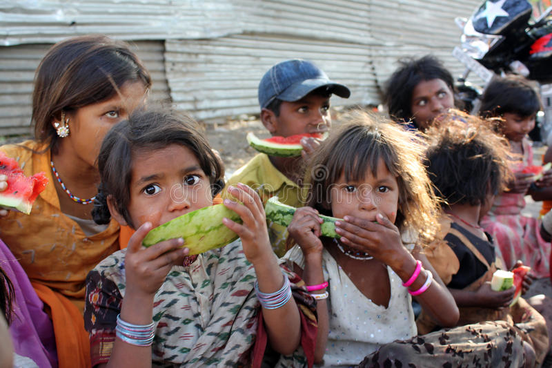 Poor Hungry Children. A poor girl in India eating a eatermelon along with her other family who spend their time begging on the streets. Focus on the eyes of the stock image