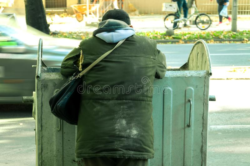 Poor and hungry homeless man in dirty clothes looking for food in the dumpster on the urban street in the city. stock image