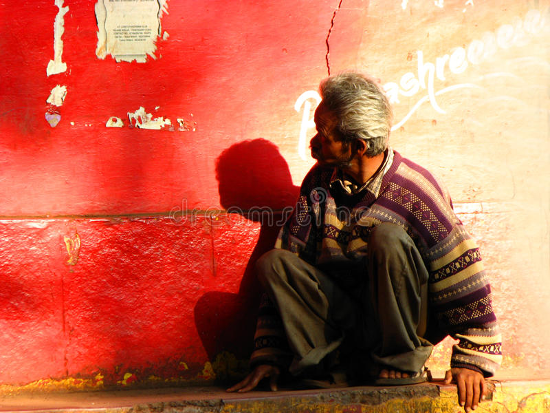 Poor Indian Man. Mahabaleshwar India - Jan 16, 2009 : A poor Indian man looks at a notice on a red wall stock photo