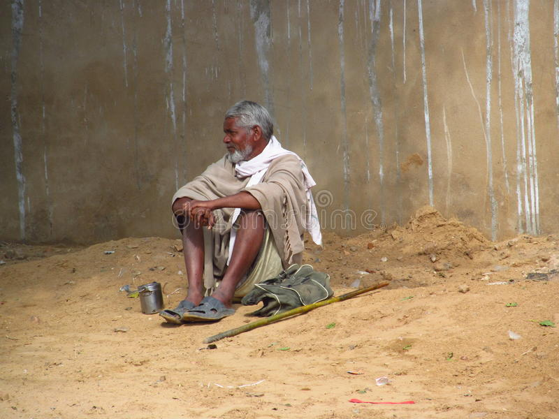 Poor indian man with a beard begging for the money on the street. Poor indian people, beggar and children dressed in the old dirty clothes living in a shack in stock photo