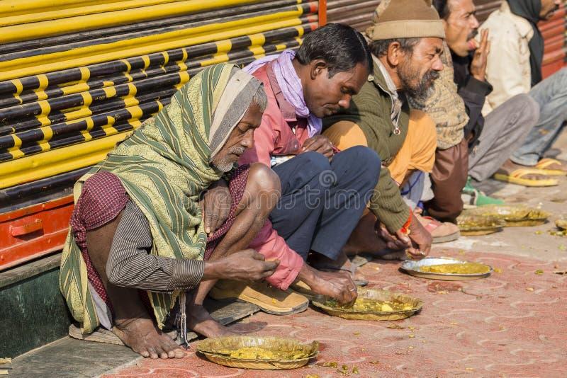 Poor indian people eating free food at the street in Varanasi, India. VARANASI, INDIA - JANUARY 25, 2017 : Unidentified poor indian people eating free food at stock image