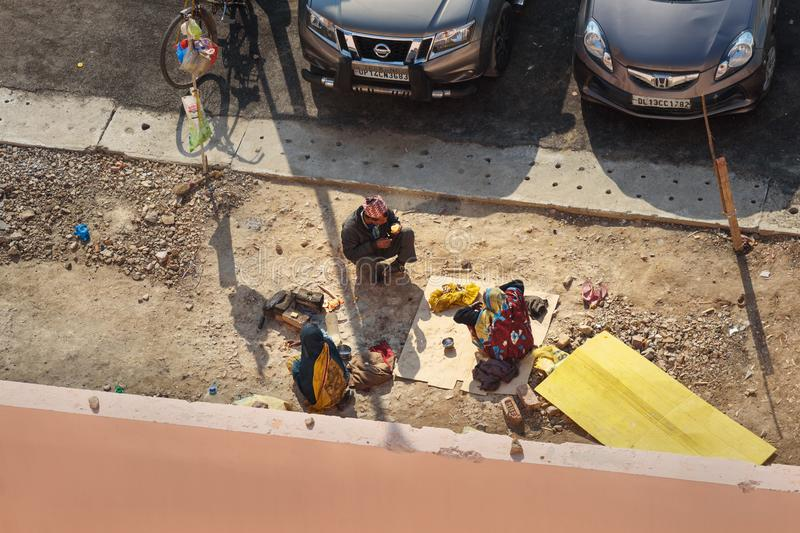 Poor Indian people having lunch on the street in New Delhi. India. Top view. India, New Delhi - January 29, 2019: Poor Indian people having lunch on the street royalty free stock photos