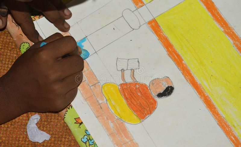 Poor Indian primary school kid drawing in a Sit and draw compitition. In West Bengal, India, child, person, girl, face, art, paper, education, kindergarten stock image
