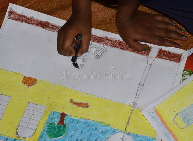 Poor Indian primary school kid drawing in a Sit and draw compitition. In West Bengal, India, child, person, girl, face, art, paper, education, kindergarten stock images