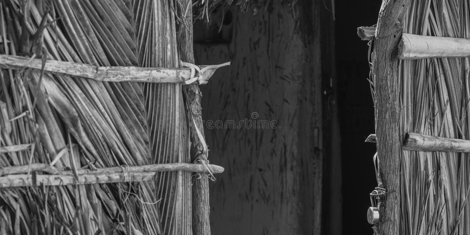 Poor indian village houses, closeup hut door, black and white stock photo