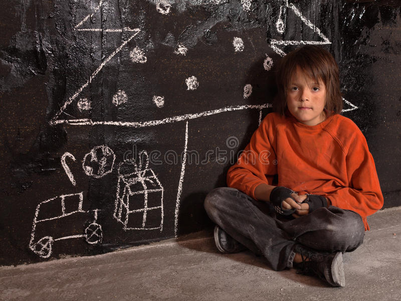 Poor kid at Christmas time on the street. Sitting alone stock photography