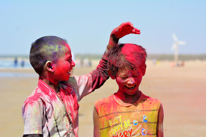 Poor kids playing holi / Mandvi, Kutch, India - March 2017 - Two poor children royalty free stock image