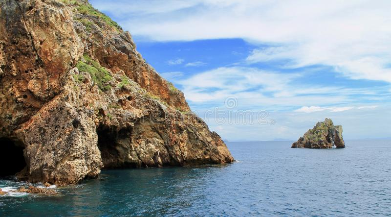 POOR KNIGHTS ISLANDS, SEA CAVE AND SQUIRE ISLAND, NEW ZEALAND. The Poor Knights are a group of islands and marine reserve located off the east coast of the royalty free stock photography