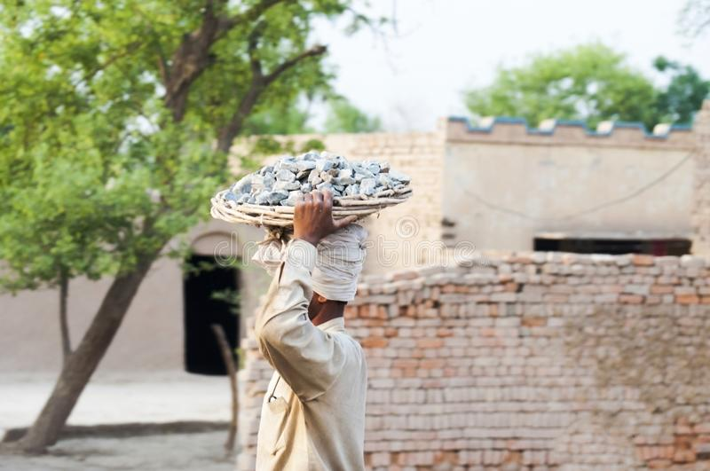 A poor labor carrying the stone crush. A laborer is walking around the mud houses stock photo