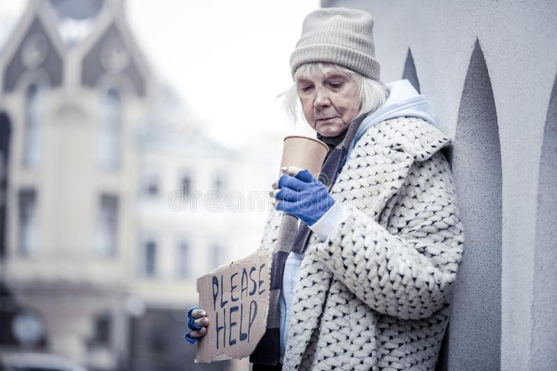 Unhappy homeless woman begging people for money. Poor life. Unhappy homeless woman standing with a plastic cup while begging people for money stock image