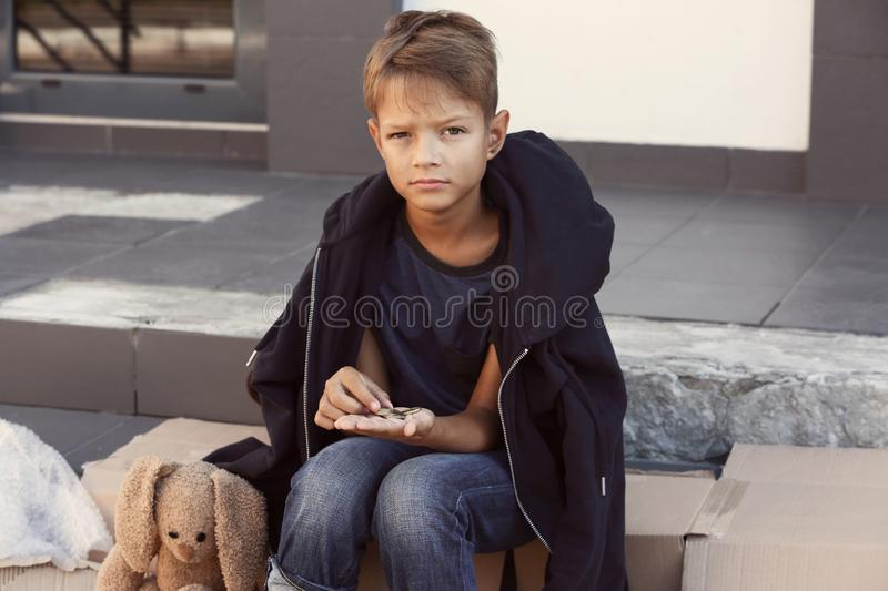 Poor little boy counting coins on street royalty free stock images