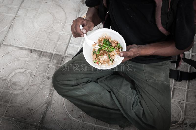 Poor man homeless with dirty hands eating eating food at street road floor in the city modern capitalism society. Poor man homeless with dirty hands eating stock photo