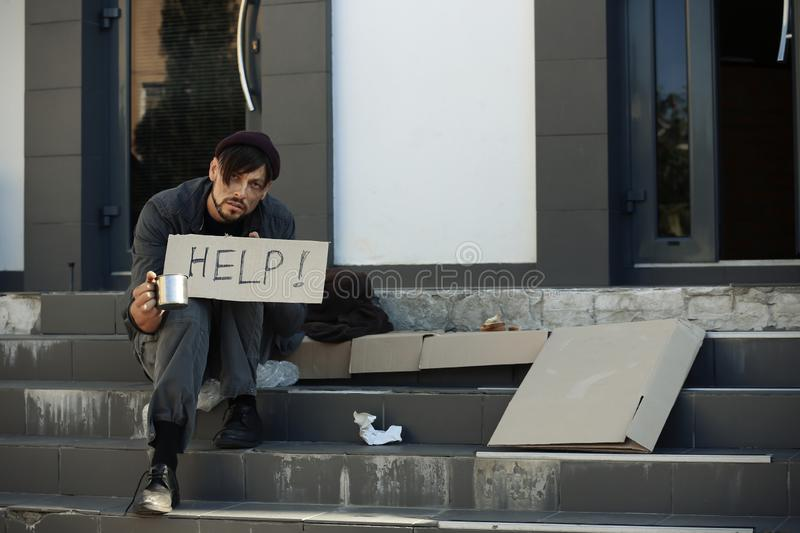 Poor man with mug begging and asking for help royalty free stock photos
