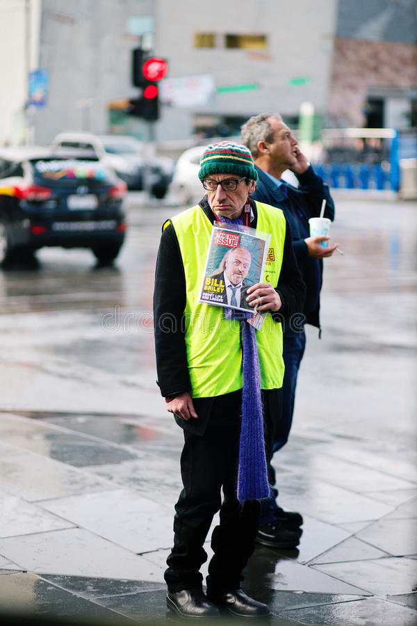 Poor man rich man. A poor street seller near Melbourne Flinders Street Station with business man standing behind him, on a cold winters day stock images