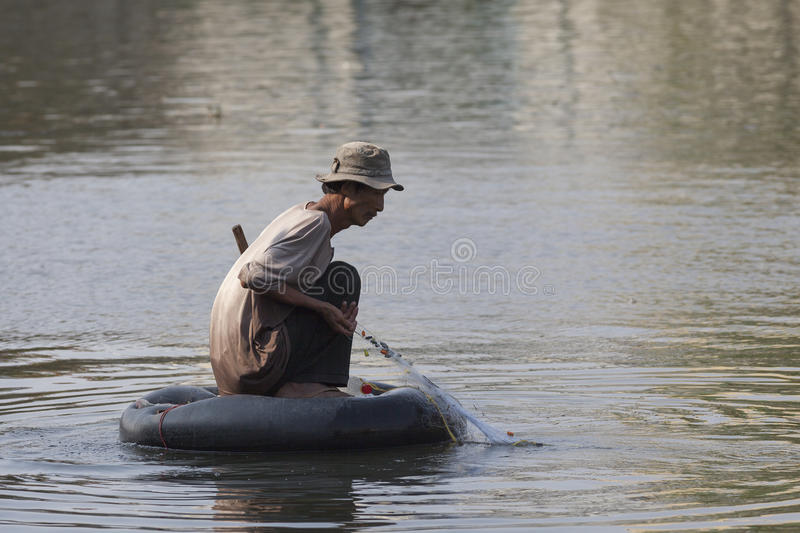 Poor man at Saigon river. Poor man fishing at Saigon river using inner tube of truck tire instead of boat royalty free stock images