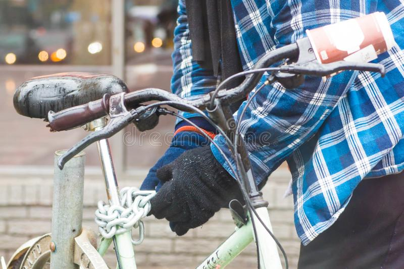 Poor man locking his bicycle on the street of Toronto royalty free stock images