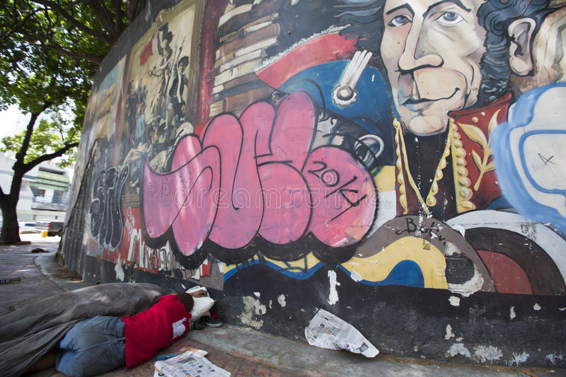 Poor man sleeping on the floor with Simon Bolivar graffiti, Cara stock photos