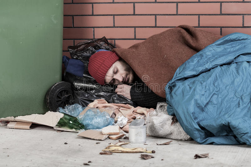 Poor man sleeping on the street. Horizontal stock image
