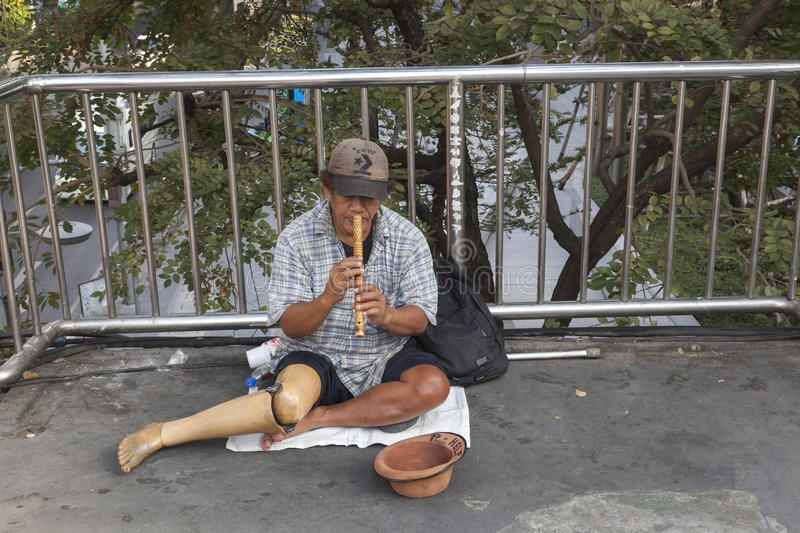 Poor man in Bangkok. Bangkok is city of rich and poor. Poor man without leg making his living with playing flute stock photography