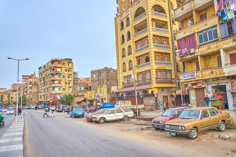 The poor neighborhood of Cairo, Egypt. CAIRO, EGYPT - DECEMBER 23, 2017: The shabby housing of poor neighborhood El-Gamaleya of Cairo with old rusty cars parked royalty free stock images