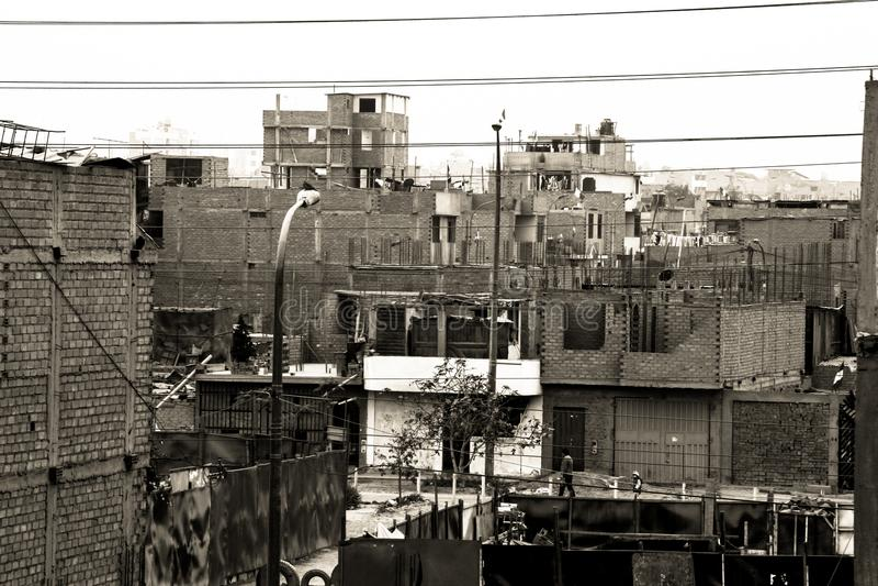 A poor neighborhood full of half dilapidated and old houses. A poor neighborhood full of dilapidated and old houses in Lima Perú,lanterns,roofs,windows,trees stock photo