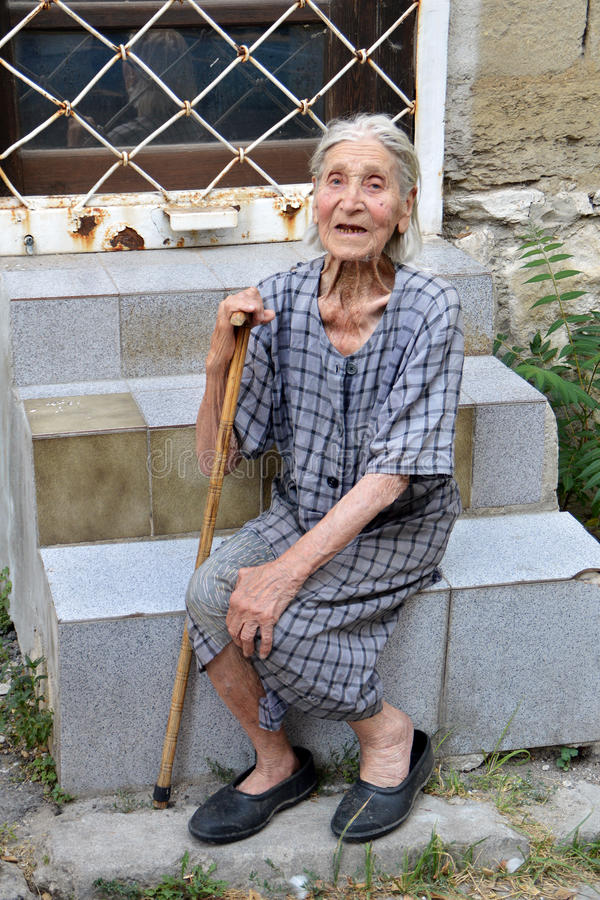 Poor old Bulgarian woman with walking cane and worn out, shabby dress sitting on stairs on the street of Varna royalty free stock photography