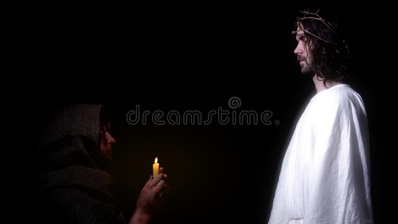 Poor old man praying with candle to appeared Jesus, salvation of righteous soul royalty free stock photography