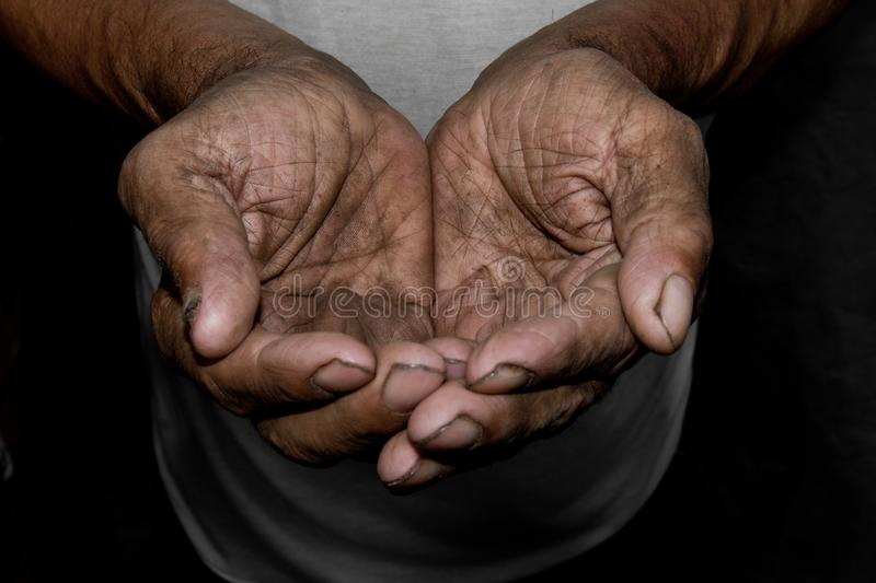 The poor old man`s hands beg you for help. The concept of hunger or poverty. Selective focus. stock photo