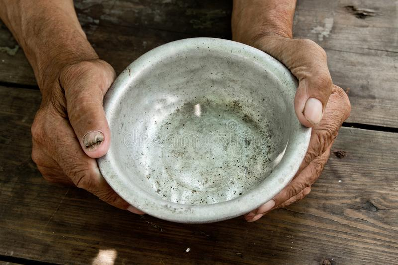 The poor old man& x27;s hands hold an empty bowl of beg you for help. royalty free stock images