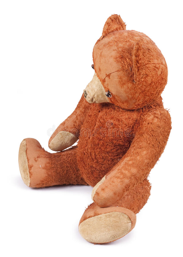 Poor old Taddy bear. Antique Teddy bear wears his ragged fur and looks abandoned. Photo isolated on white background royalty free stock images