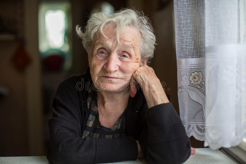 Poor old woman in her home. Looking into the camera royalty free stock photos