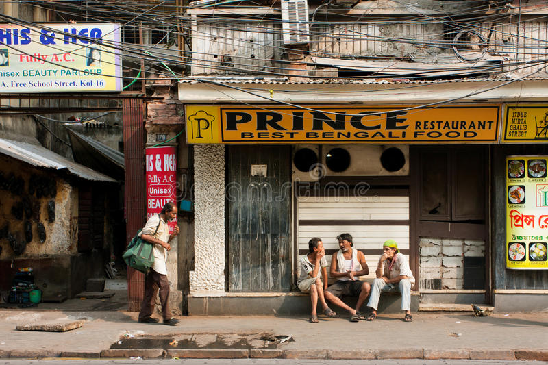 Poor people chating at front of indian cuisine restaurant. KOLKATA, INDIA: Poor people chating at front of indian cuisine restaurant. Third biggest indian city stock image