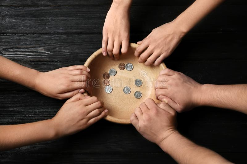 Poor people holding bowl with coins on wooden background. Top view royalty free stock images
