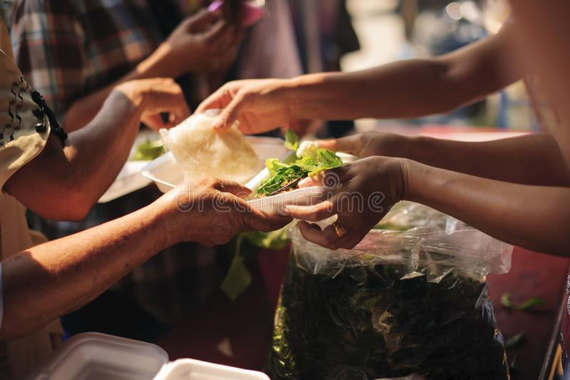 Poor people receive donated food from donors, Demonstrate mutual sharing in today`s society : Beggar begs food from donors stock photo