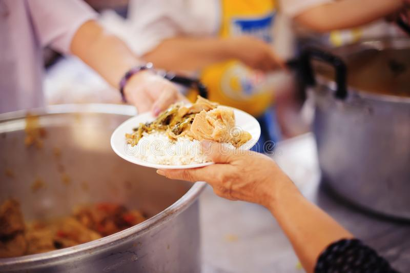Poor people receiving food from donations : the concept of social sharing.  stock image