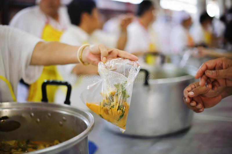 Poor people receiving food from donations : the concept of social sharing.  stock photo