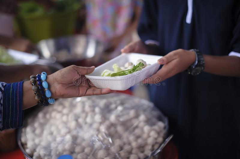 Poor people receiving food from donations : Homeless people are helped with food relief, famine relief : volunteers giving food to. Poor people in desperate royalty free stock photos